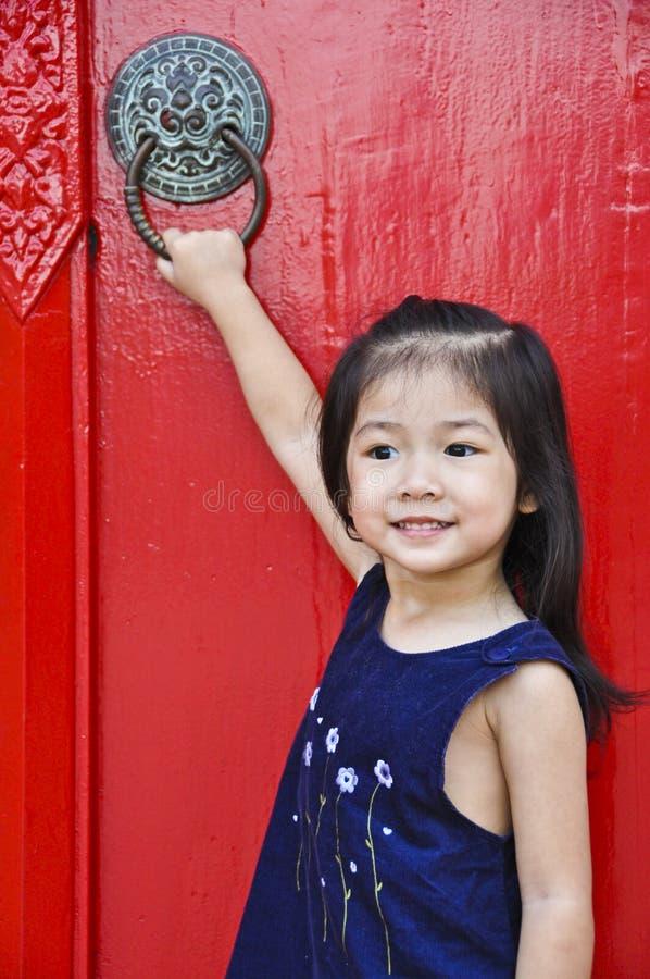 Piccola ragazza asiatica davanti alla porta rossa antica. immagine stock