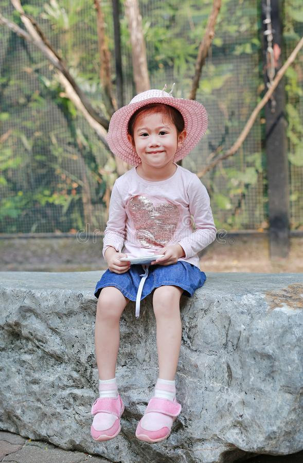 Piccola ragazza asiatica sveglia che porta il cappello di paglia rosa che si siede sulla pietra contro il giardino pubblico verde immagine stock libera da diritti