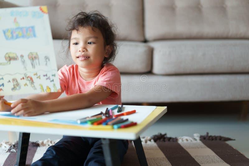Piccola ragazza asiatica sveglia che si siede tenendo una carta da disegno, un compito di disegno e una scrittura con i pastelli  fotografia stock