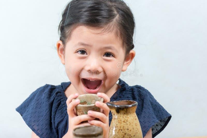 Piccola ragazza asiatica sveglia che sorride e che tiene tazza ceramica o disponibila immagini stock libere da diritti