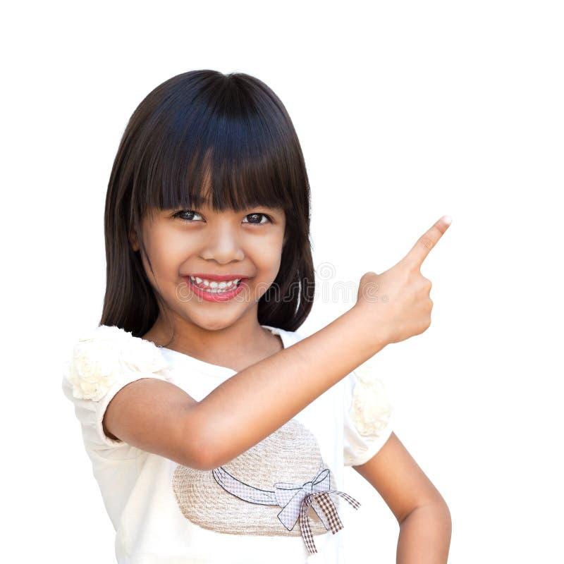 Piccola ragazza asiatica sveglia con il dito indice su fotografia stock