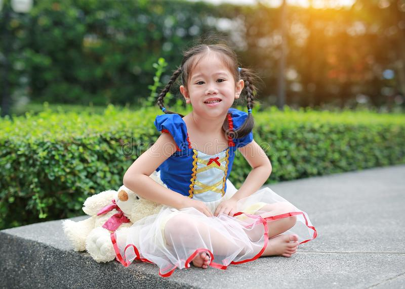 Piccola ragazza asiatica sveglia vestita con un'attrezzatura di fantasia che si siede nel giardino immagini stock libere da diritti