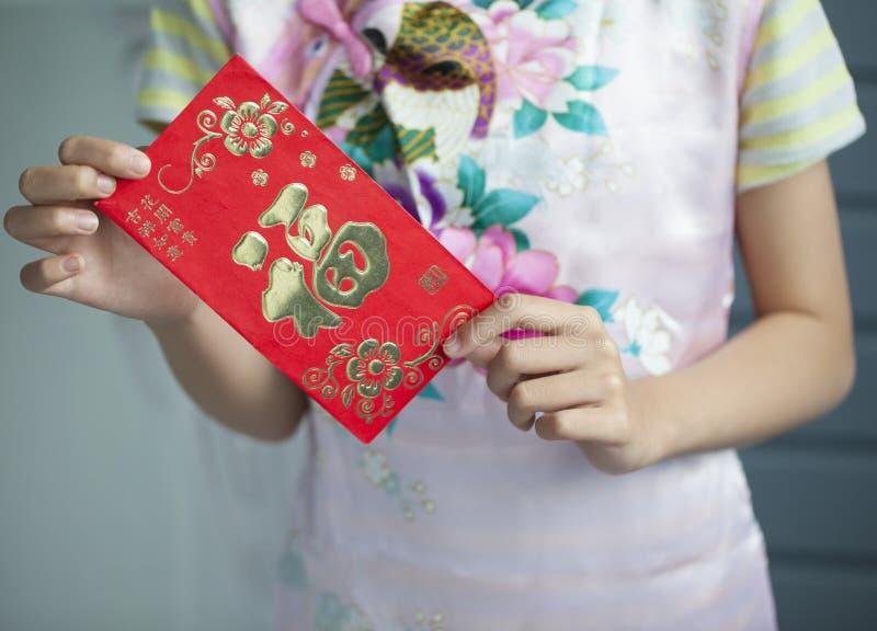 Piccola ragazza asiatica in vestito tradizionale cinese e nella tenuta della e rossa fotografia stock