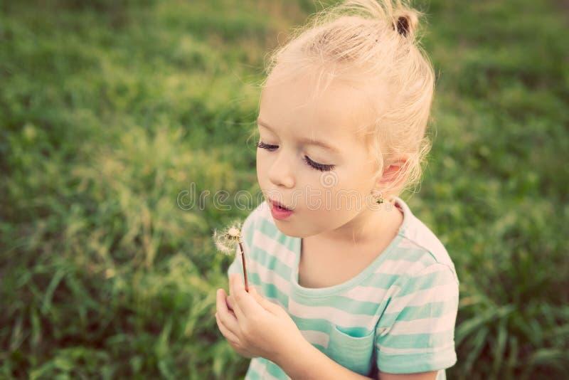 Piccola ragazza bionda adorabile con il fiore del dente di leone immagini stock