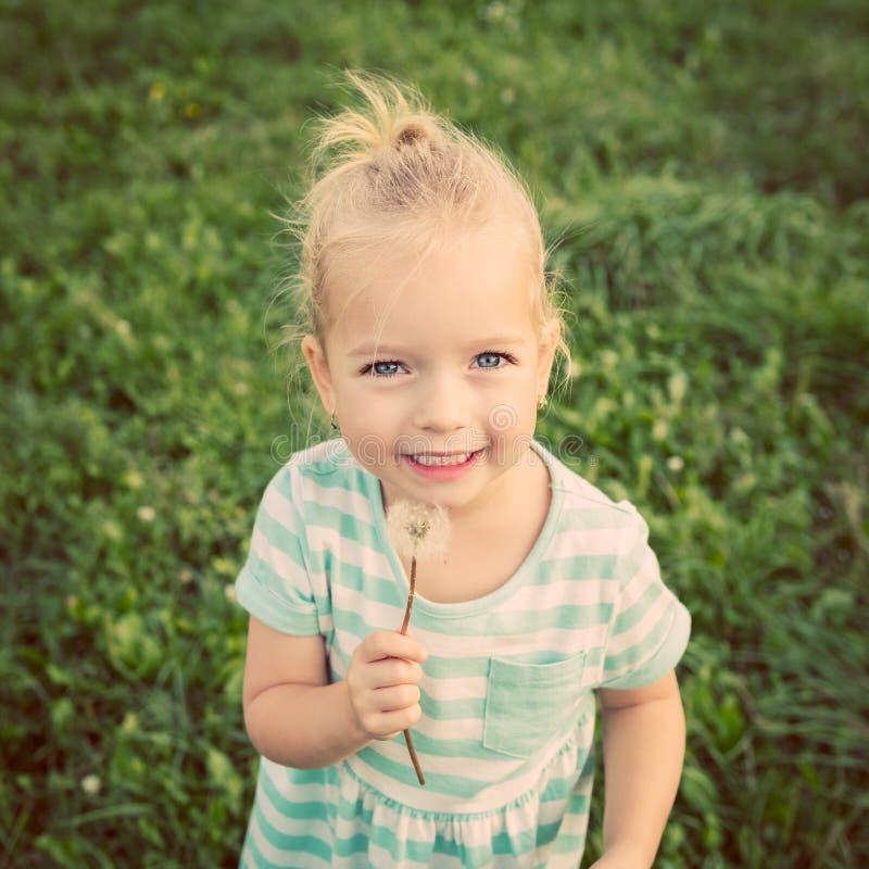 Piccola ragazza bionda adorabile con il fiore del dente di leone immagine stock libera da diritti
