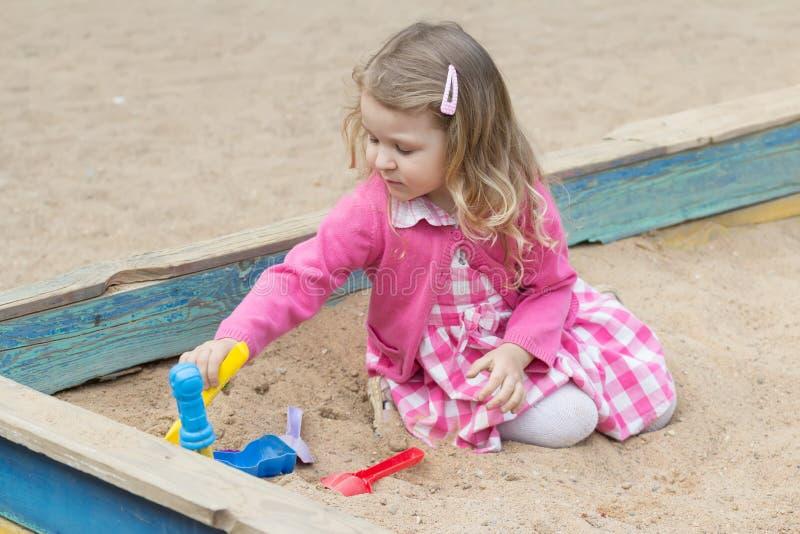 Piccola ragazza bionda che gioca in sabbiera con gli strumenti di plastica del giocattolo immagine stock libera da diritti