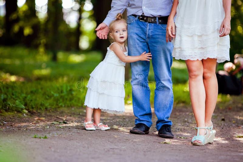 Piccola ragazza bionda molto sveglia che tiene la mamma ed il papà del piede fotografie stock