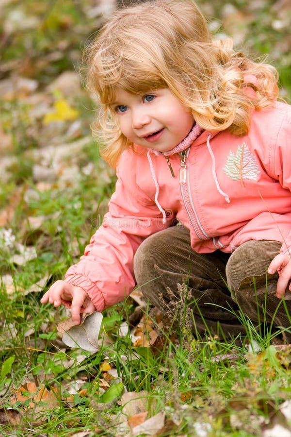 Piccola ragazza bionda nella sosta di autunno fotografia stock libera da diritti