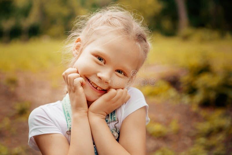 Piccola ragazza bionda sorridente adorabile con capelli intrecciati Bambino sveglio divertendosi un giorno di estate soleggiato a fotografia stock libera da diritti