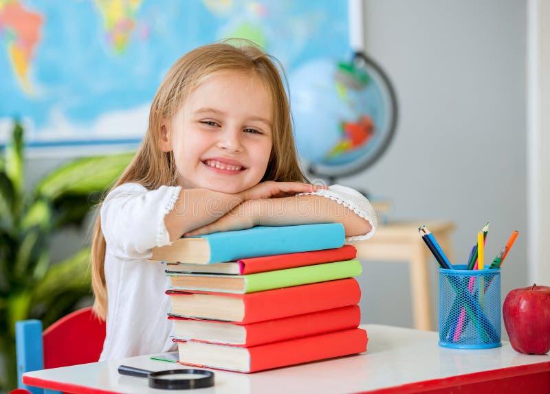 Piccola ragazza bionda sorridente che si tiene per mano sui libri nell'aula della scuola fotografia stock libera da diritti
