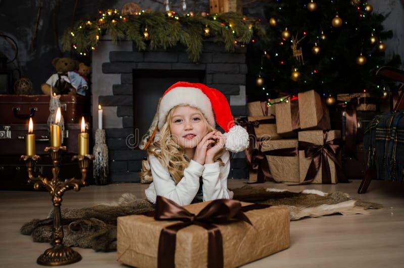 Piccola ragazza bionda sveglia che ha un regalo in sue mani su un fondo di natale Concetto 'nucleo familiare' felice immagini stock libere da diritti