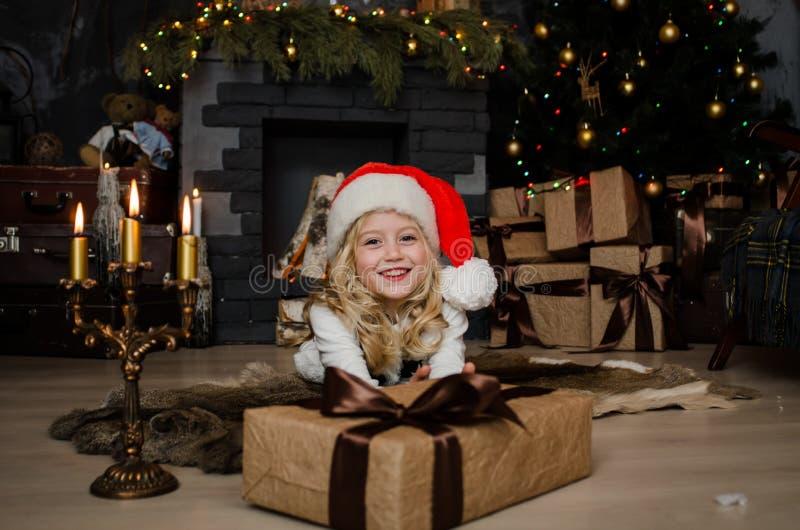 Piccola ragazza bionda sveglia che ha un regalo in sue mani su un fondo di natale Concetto 'nucleo familiare' felice fotografie stock