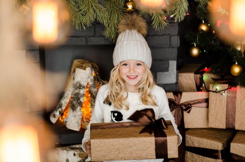 Piccola ragazza bionda sveglia che ha un regalo in sue mani su un fondo di natale Concetto 'nucleo familiare' felice immagini stock