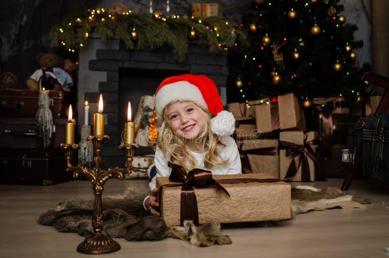 Piccola ragazza bionda sveglia che ha un regalo in sue mani su un fondo di natale Concetto 'nucleo familiare' felice fotografia stock
