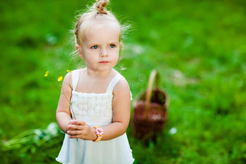Piccola ragazza bionda sveglia in un vestito bianco che tiene un fiore nel suo immagini stock libere da diritti