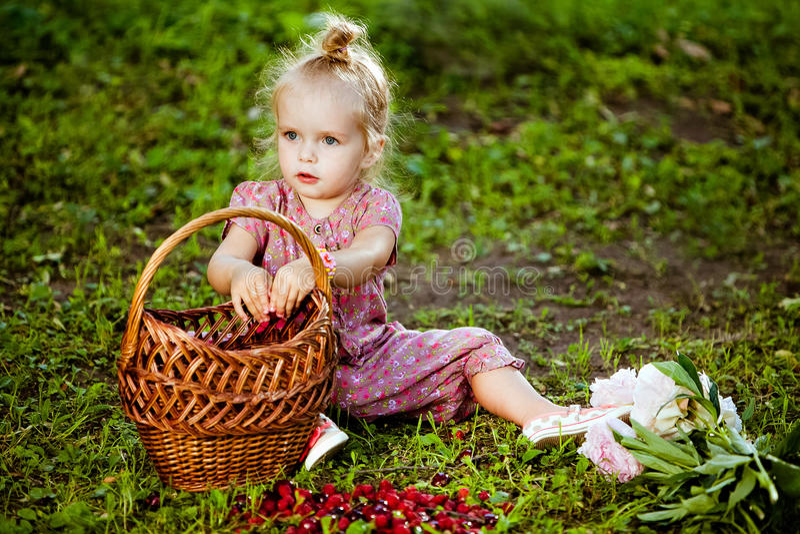Piccola ragazza bionda sveglia in una tuta rosa che mangia i lamponi franco immagine stock