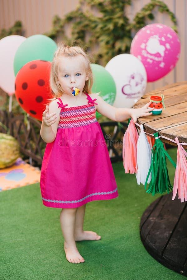 Piccola ragazza bionda in un vestito rosa che sta nel cortile con i palloni variopinti fotografie stock