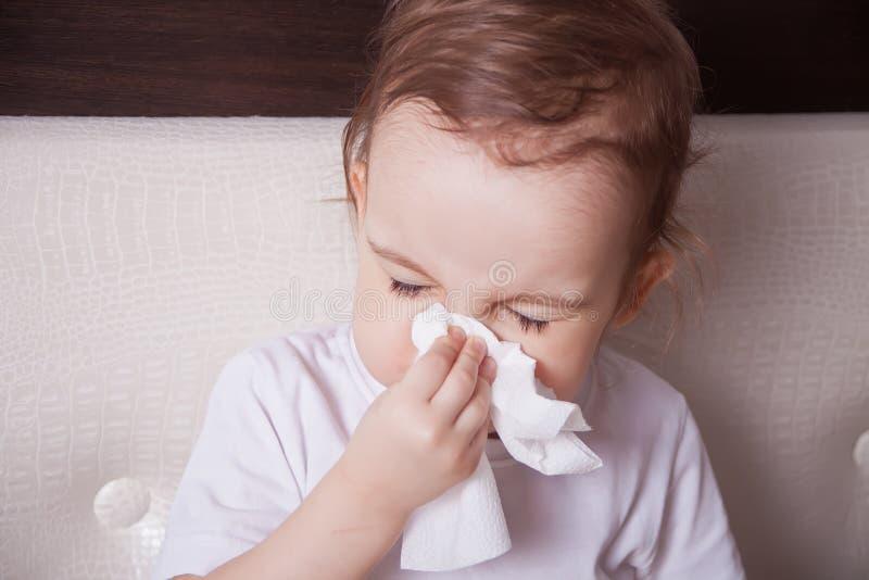 Piccola ragazza castana malata che soffia il suo naso fotografia stock