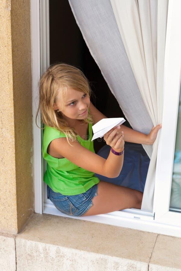 Piccola ragazza caucasica con l'aereo di carta in finestra fotografia stock libera da diritti