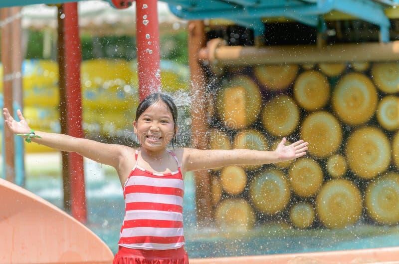 Piccola ragazza caucasica felice che gioca acqua al aquapark fotografie stock libere da diritti