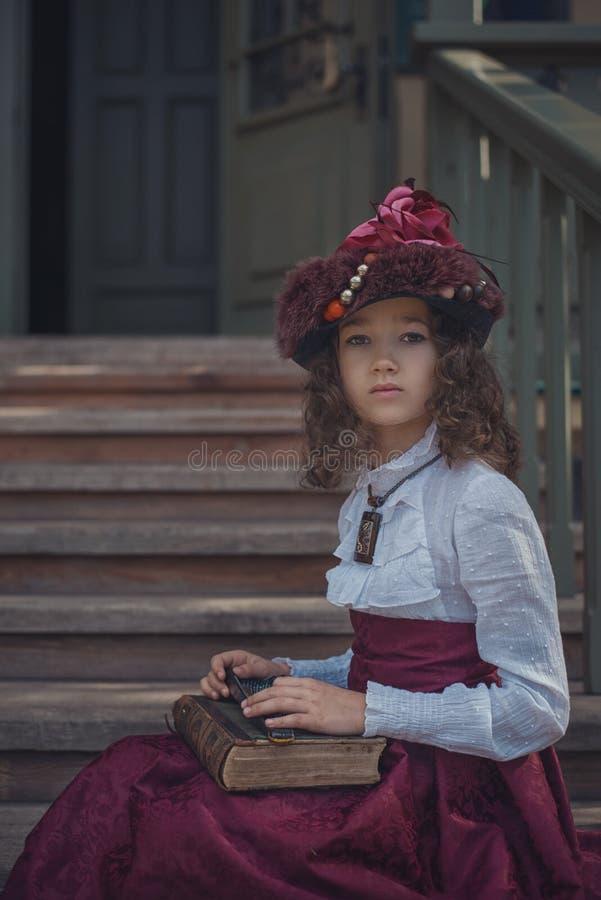 Piccola ragazza caucasica sveglia che indossa i retro vestiti Bambino femminile piacevole in bello vestito d'annata immagine stock