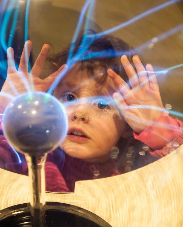 Piccola ragazza che esamina una palla del plasma fotografia stock