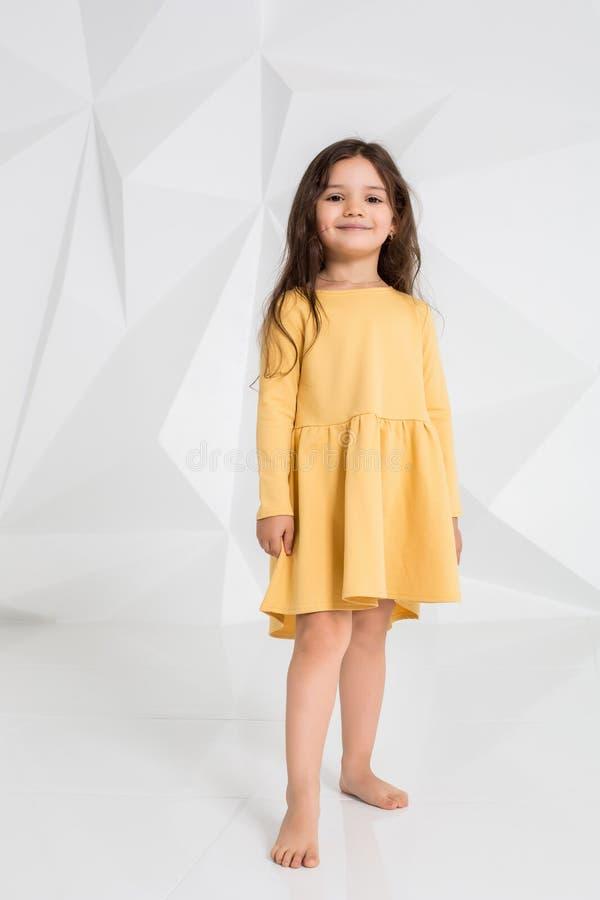 Piccola ragazza che indossa dancing giallo del vestito nello studio contro il fondo bianco immagine stock libera da diritti