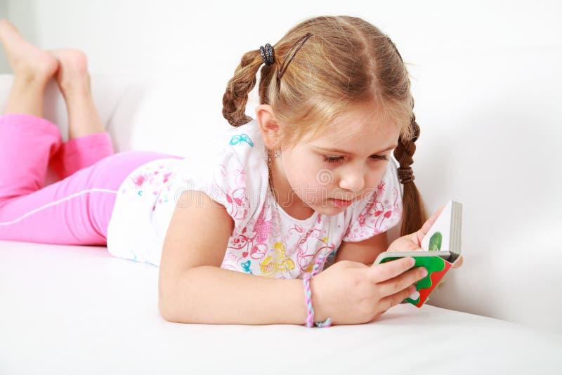 Piccola ragazza che si rilassa e che legge fotografie stock libere da diritti