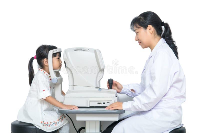 Piccola ragazza cinese asiatica che fa l'esame di occhi con automatico con riferimento a fotografia stock