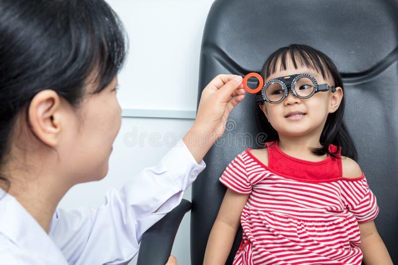 Piccola ragazza cinese asiatica che fa l'esame di occhi dal ophthalmolog fotografia stock