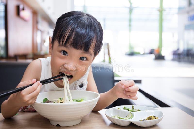 Piccola ragazza cinese asiatica che mangia la minestra di tagliatelle del manzo fotografie stock