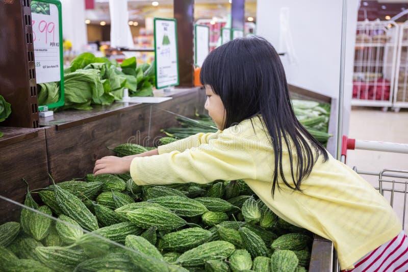 Piccola ragazza cinese asiatica che sceglie le verdure fotografia stock