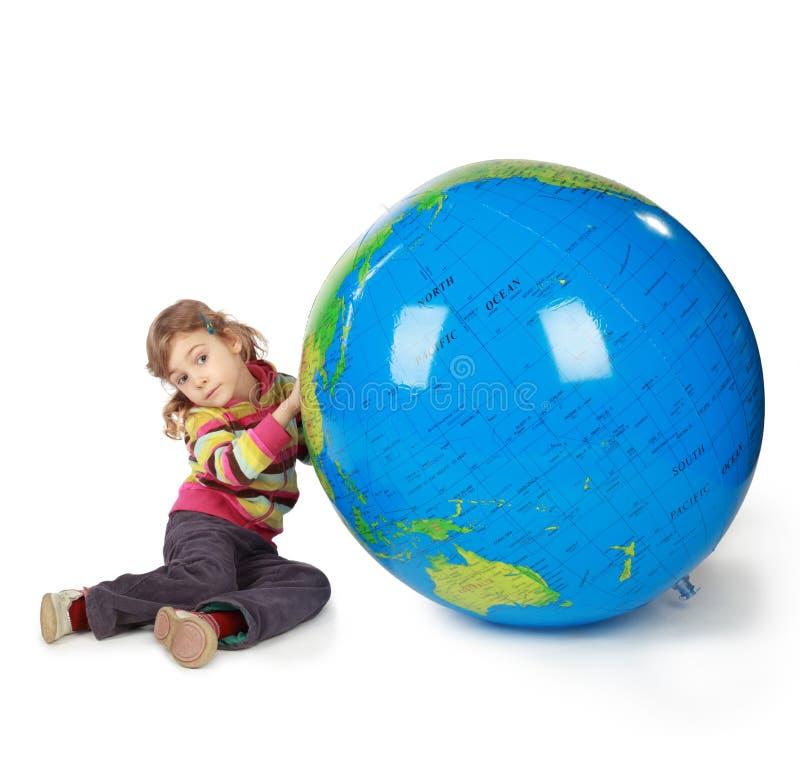 Piccola ragazza con il globo enorme su bianco fotografia stock libera da diritti