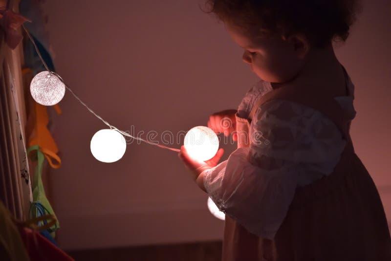 Piccola ragazza con le luci dell'albero di Natale fotografia stock