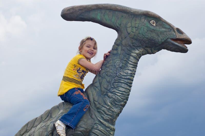 Piccola ragazza coraggiosa su un dinosauro in una sosta immagini stock
