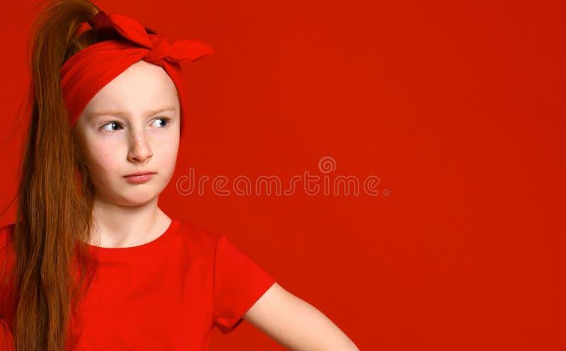 Piccola ragazza dai capelli rossi sveglia che tene il broncio e che aggrotta le sopracciglia mentre tenendosi per mano sulla vita fotografie stock