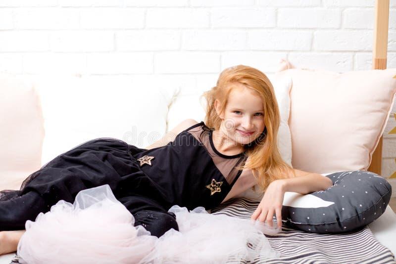 Piccola ragazza dai capelli rossi sveglia in vestiti di modo che posano alla macchina fotografica fotografia stock