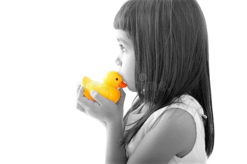 Piccola ragazza del bambino che bacia un'anatra gialla del bagno fotografia stock