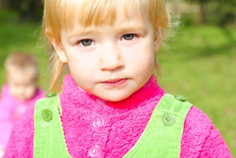 Piccola ragazza del ritratto sull'erba verde entro l'autunno fotografia stock libera da diritti
