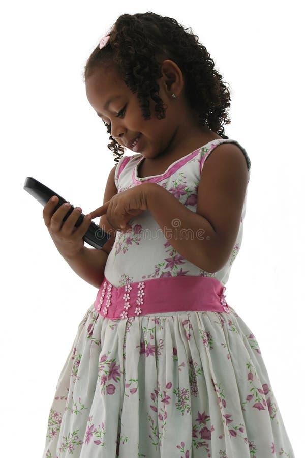 Piccola ragazza dell'afroamericano in vestito con il telefono fotografie stock libere da diritti