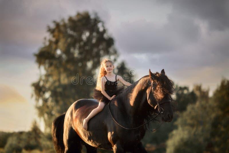 Piccola ragazza della ballerina con lo stallone frisone nero immagini stock libere da diritti