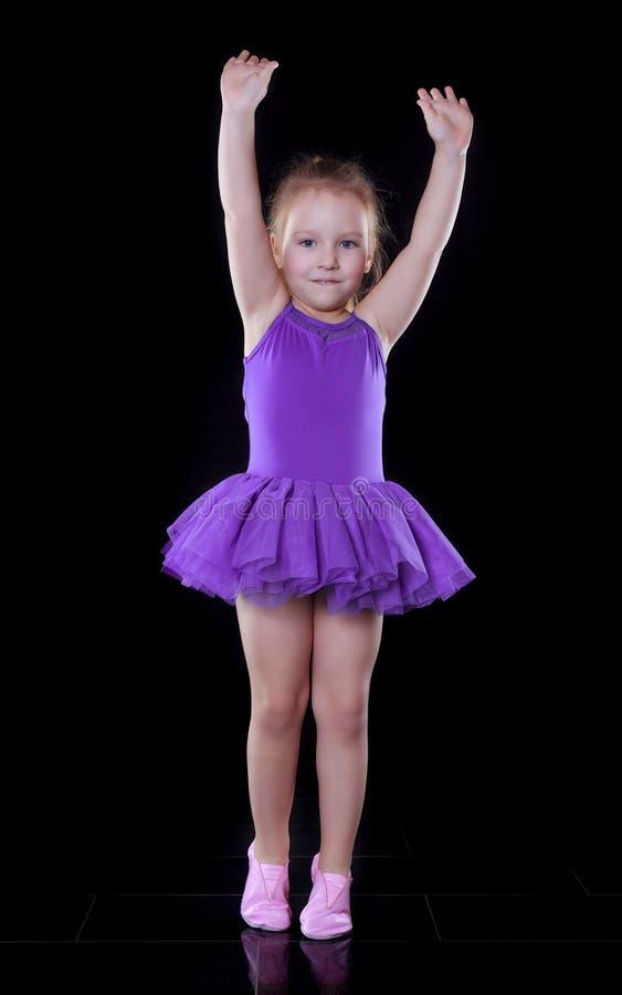 Piccola ragazza della ballerina in un dancing porpora del tutu in una stanza scura immagine stock