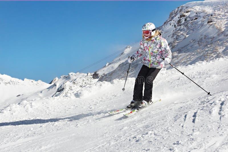 Piccola ragazza dello sciatore nel pendio delle alpi della neve fotografia stock libera da diritti