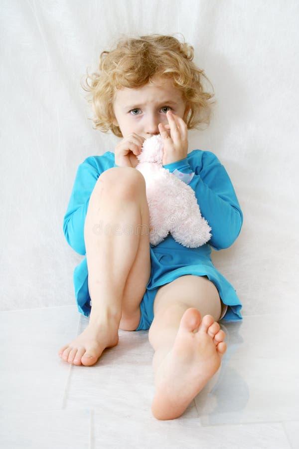 Piccola ragazza di seduta riccia bionda triste sul bianco con il giocattolo immagine stock
