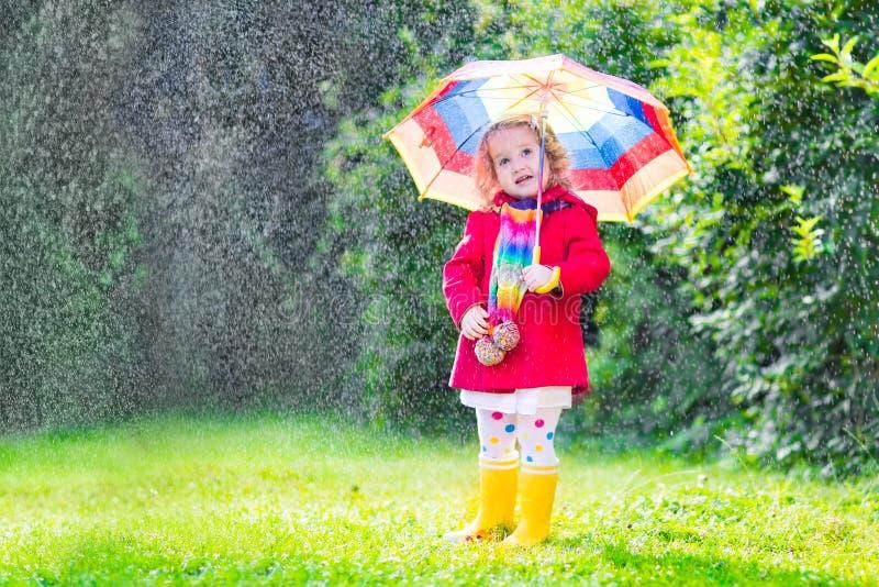 Piccola ragazza divertente che gioca nella pioggia fotografie stock libere da diritti