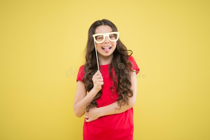 Piccola ragazza divertente che tiene i puntelli della cabina della foto di vetro sul bastone Bambino sveglio con i puntelli del p fotografia stock libera da diritti