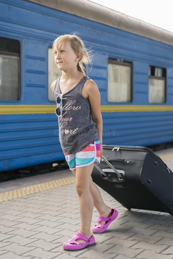 Piccola ragazza dolce con una grande valigia su una piattaforma ferroviaria abbandonata ragazza che tira una grande valigia sulla fotografia stock libera da diritti