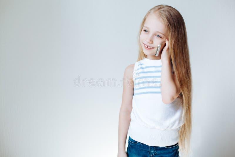 Piccola ragazza europea bionda sveglia in abbigliamento casual che parla sul telefono cellulare e sul sorridere Priorità bassa bi fotografie stock libere da diritti