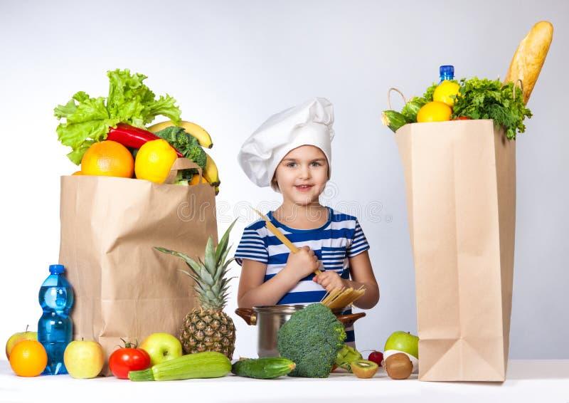 Piccola ragazza felice in cappello del cuoco unico con le grandi borse dei prodotti Tiene nelle mani degli spaghetti immagini stock