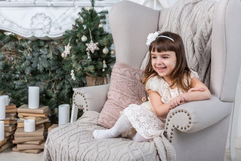 Piccola ragazza felice che si siede sulla grande poltrona accogliente immagine stock libera da diritti